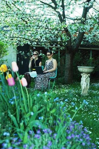 Two women sitting in garden using laptop computer and landline phone : Stock Photo