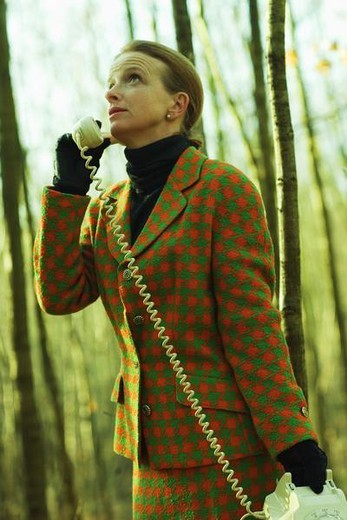 Woman standing in woods, using landline phone, looking up : Stock Photo