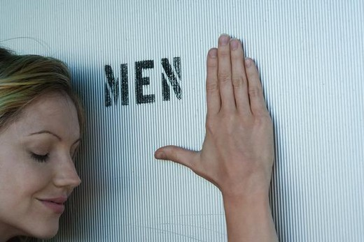 Woman resting head and hand against men's room door, eyes closed : Stock Photo
