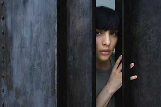 Woman opening door, looking out at camera : Stock Photo