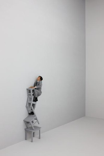 Businessman climbing ladder made of stacked chairs : Stock Photo