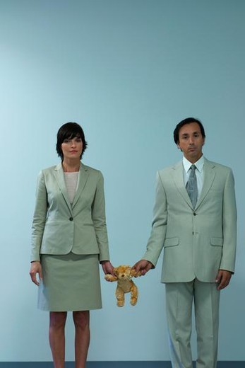 Professional couple standing together holding teddy bear between them : Stock Photo