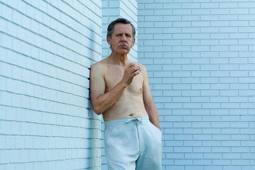 Bare-chested man leaning against wall smoking, exhaling : Stock Photo