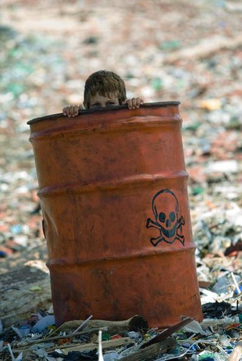 Child peeking over edge of metal barrel marked with skull and bones, surrounded by landfill : Stock Photo