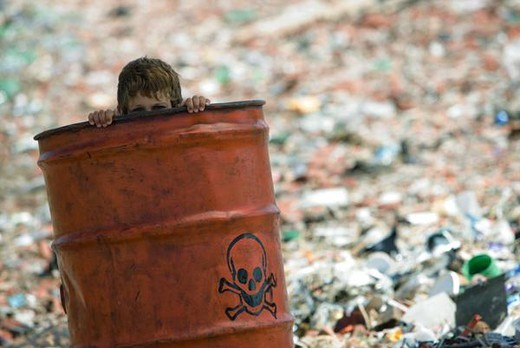 Stock Photo: 4276-3235 Child peeking over edge of metal barrel marked with skull and bones, surrounded by landfill