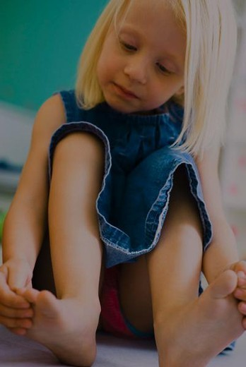 Stock Photo: 4276-3270 Little girl sitting on floor touching toes