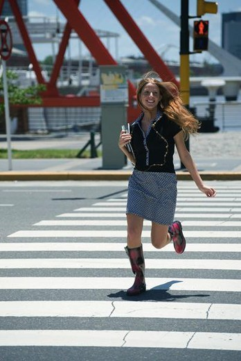 Stock Photo: 4276-3284 Young woman running across crosswalk while walk signal is red