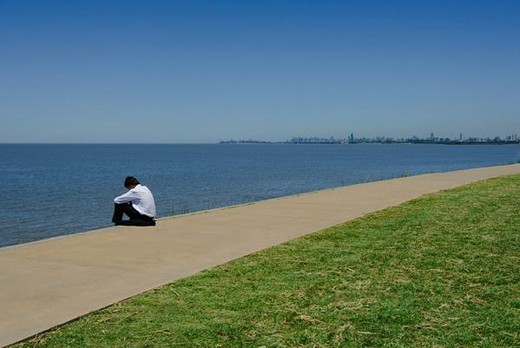 Stock Photo: 4276-3411 Man in business attire sitting by sea with head down