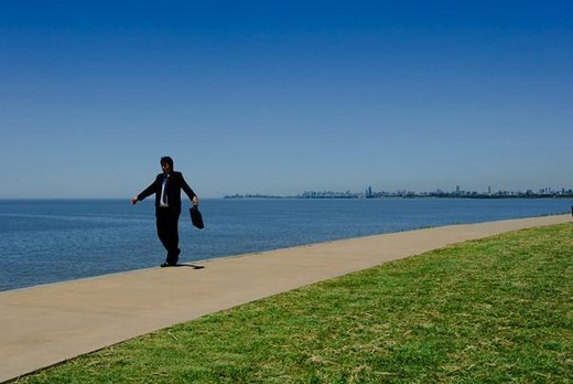 Businessman walking along edge of sidewalk along sea, arms out : Stock Photo