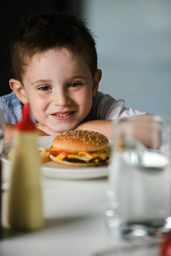 Stock Photo: 4276-3592 Little boy sitting at table with head resting on arms, looking at cheeseburger