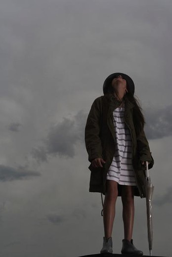 Female with umbrella looking up at cloudy sky : Stock Photo
