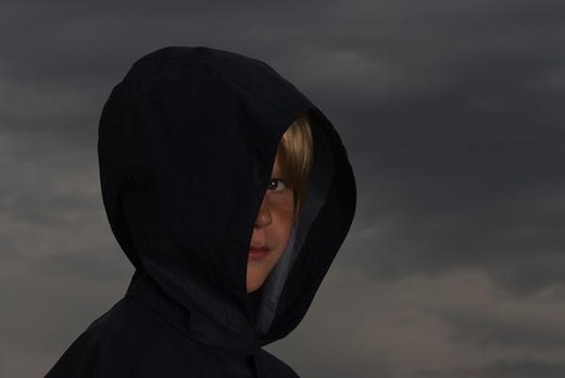 Boy with face partially obscured by jacket hood, looking at camera : Stock Photo