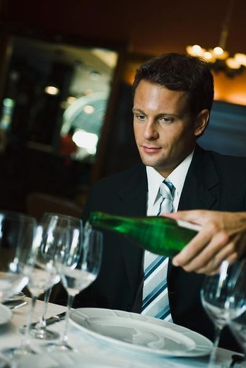 Man in fine restaurant watching as waiter pours wine : Stock Photo
