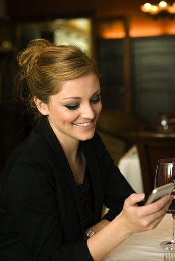 Stock Photo: 4276-4563 Woman text messaging in restaurant