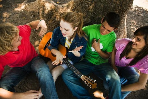 Stock Photo: 4276-4579 Young friends chatting together, one holding acoustic guitar