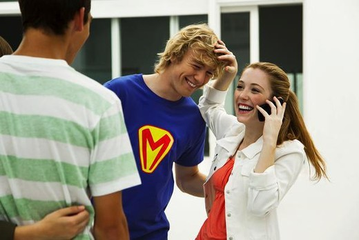 Stock Photo: 4276-4604 Young friends hanging out, one talking on cell phone