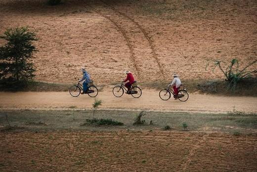 Bagan, Myanmar, people riding bicycles on dirt road : Stock Photo
