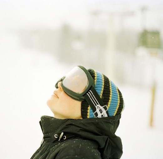 Woman wearing ski goggles looking up : Stock Photo