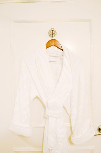 Stock Photo: 4276-5170 White bathrobe hanging on back of door