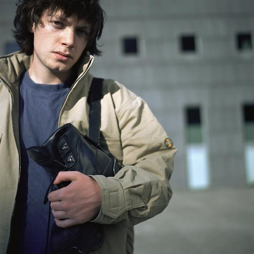 Urban scene, young man holding in-line skate : Stock Photo
