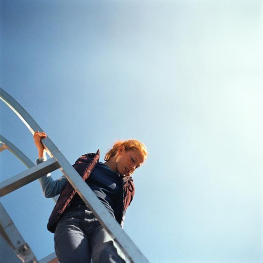 Stock Photo: 4276-7000 Young woman on ladder, low angle view