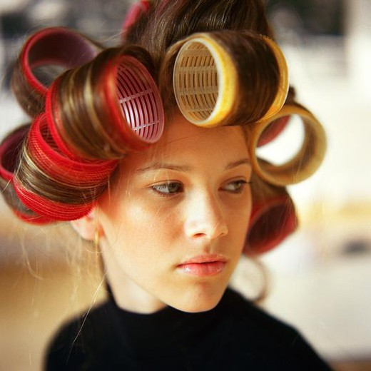 Young woman with rollers in hair : Stock Photo