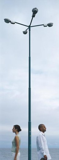 Man and woman standing back to back, on either side of lamp post : Stock Photo