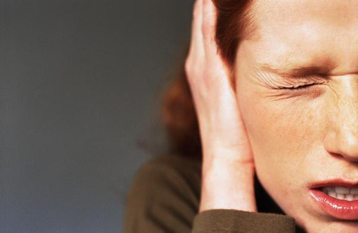 Stock Photo: 4276-7886 Young woman squinting eye closed, hand covering ear, close-up