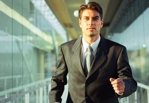 Young businessman running in office corridor : Stock Photo