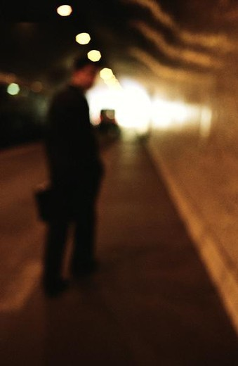 Man standing in tunnel, blurred : Stock Photo
