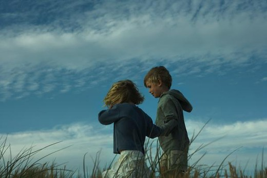 Stock Photo: 4276-8046 Boy and girl walking side by side through tall grass, holding hands