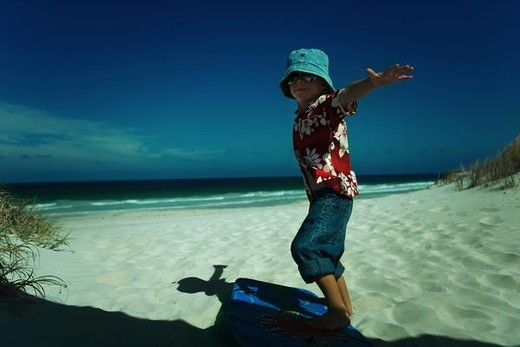 Stock Photo: 4276-8055 Boy standing on bodyboard with arms out, side view, full length