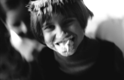 Stock Photo: 4276-8108 Child laughing with whipped cream on face, b&w