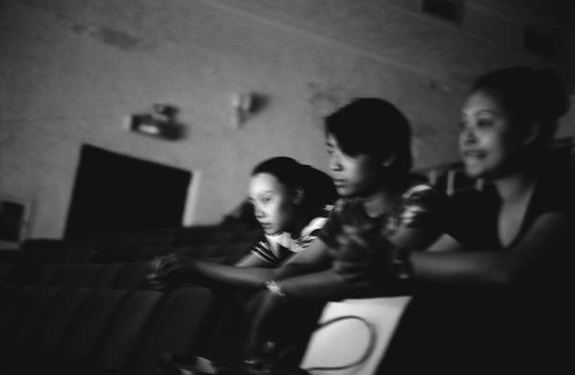 Three young people sitting in movie theater, b&w : Stock Photo
