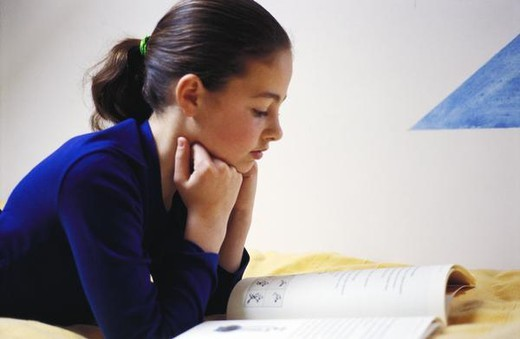 Girl reading, side view : Stock Photo