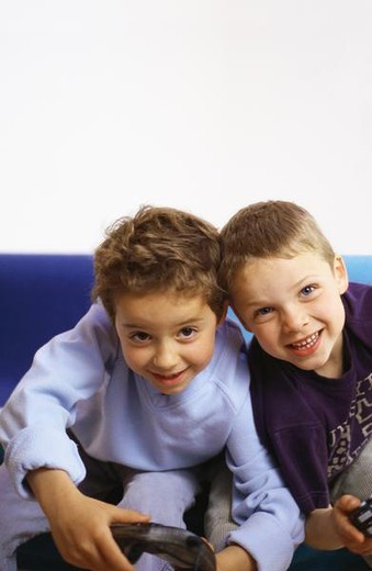 Stock Photo: 4276-8196 Two boys sitting on sofa holding joysticks, looking at camera