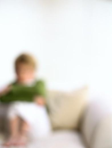 Girl sitting on sofa, defocused : Stock Photo