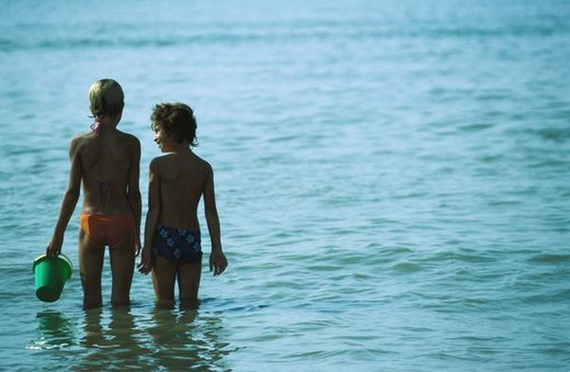 Two children standing in water, rear view : Stock Photo
