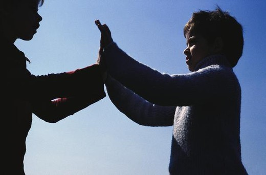 Two children playing clapping game, low angle view : Stock Photo
