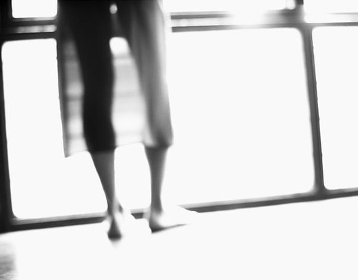 Young woman standing in front of window, low section, rear view, b&w, defocused : Stock Photo