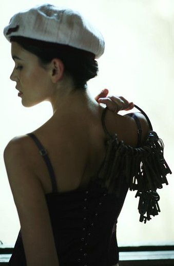 Woman wearing hat, holding keys over shoulder, rear view, close-up : Stock Photo