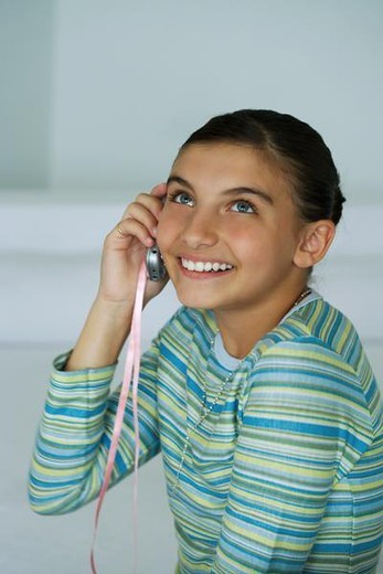 Stock Photo: 4276-8471 Preteen girl using cell phone, smiling and looking up
