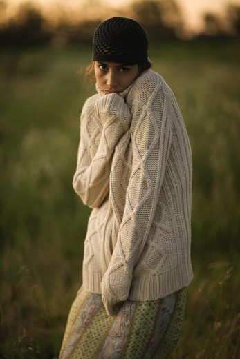 Stock Photo: 4276-8504 Woman standing outdoors wearing thick sweater, looking at camera, portrait