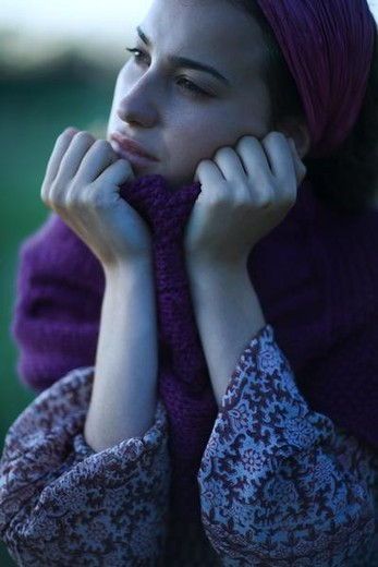 Stock Photo: 4276-8508 Woman holding sweater neck up to face, looking away, portrait