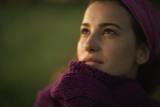 Woman pulling sweater up to face, looking up, close-up : Stock Photo