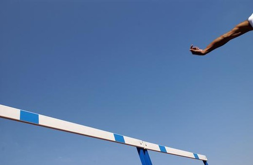 Hurdle and athlete's arm against blue sky : Stock Photo