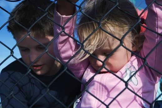 Boy and girl looking through chainlink fence, close-up : Stock Photo
