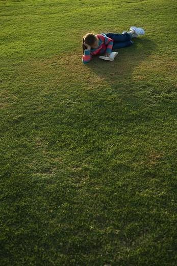 Girl lying on grass, reading book, full length : Stock Photo