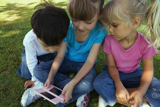 Three children sitting on grass, playing with video game, close-up : Stock Photo