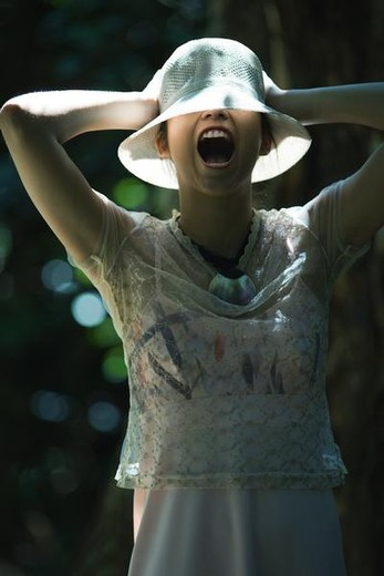 Stock Photo: 4276-9064 Young woman standing outdoors, wearing sunhat over eyes, shouting, arms raised